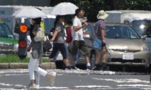 The effects of heat haze is seen as pedestrians cross a street during a heatwave in Tokyo.