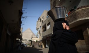A woman carries a food bowl on her head in the village of El Saman in sight of the Great Pyramid of Cheops in Giza, Egypt.